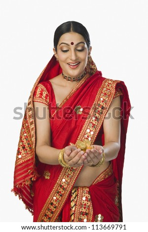 Woman in red mekhla holding gold coins