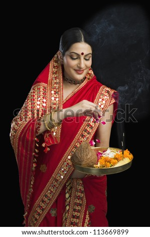 Woman in red mekhla holding religious offering