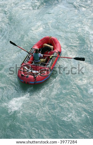 Woman in red raft with dogs and bicycle on white water rapids, Alaska - stock photo