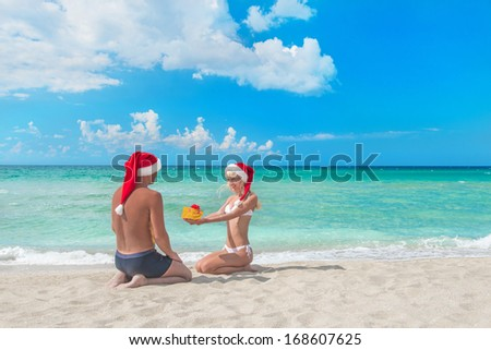woman in red santa hat  giving a present to her boyfriend on the sea beach - christmas vacations concept - stock photo