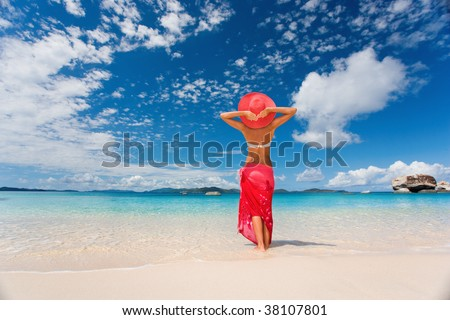 woman in red sarong on tropical beach on caribbean vacation at spring bay