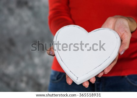 Woman in red shirt holding / giving a heart in hands. Offering love concept - stock photo