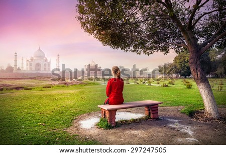 Woman in red sitting on the bench in Mehtab Bagh and looking at Taj Mahal in Agra, Uttar Pradesh, India - stock photo