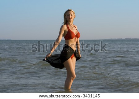 Woman in red swimming suit standing in water, looking into camera. - stock photo