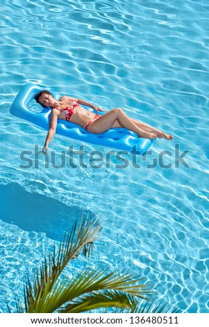 Woman in red swimsuit bakes on inflatable mattress in pool - stock photo