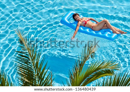 Woman in red swimsuit sunbathes on inflatable mattress in pool - stock photo