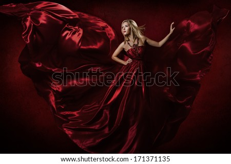 Woman in red waving dress dancing with flying fabric  - stock photo