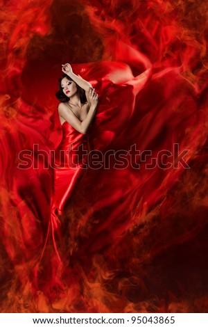 Woman in red waving silk dress as fire flame. Artistic Model girl posing in flying long gown - stock photo
