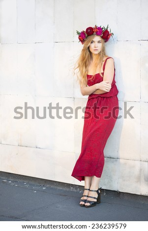 Woman in red with red flower wreath stands near white wall - stock photo
