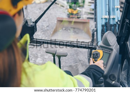 Woman in reflective clothing operating heavy equipment