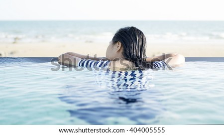 Woman in relaxing on the swimming pool, sea scenery background. - stock photo