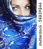Woman in religious traditional blue cape looking forward. Natural blue colors o eyes - stock photo