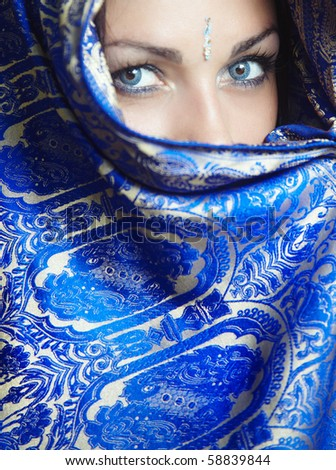 Woman in religious traditional blue cape looking forward. Natural blue colors o eyes