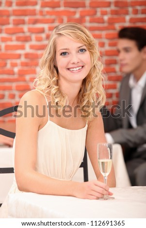 Woman in restaurant with a glass of champagne - stock photo