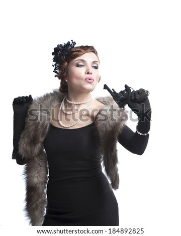 woman in retro style, wearing a black dress, fur and beads with gun ,on white background - stock photo