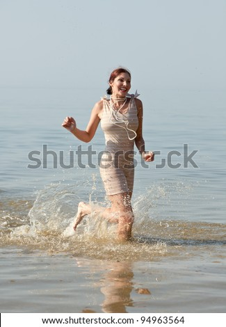 Woman in retro swimsuit smiles and runs through the water against the sea