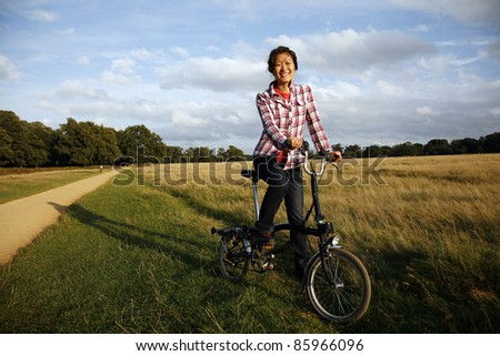 Woman in Richmond Park cycling at dusk