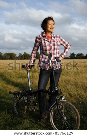 Woman in Richmond Park with bicycle at dusk - stock photo