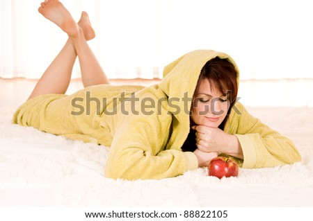 Woman in robe with  apple lying on the floor - stock photo