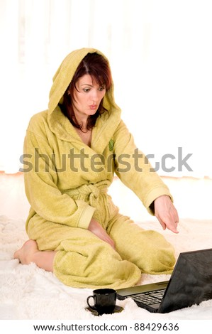 Woman in robe with laptop sitting on the floor - stock photo
