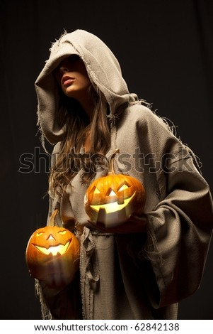 woman in robe wrapped around her head holding halloween pumpkins - stock photo