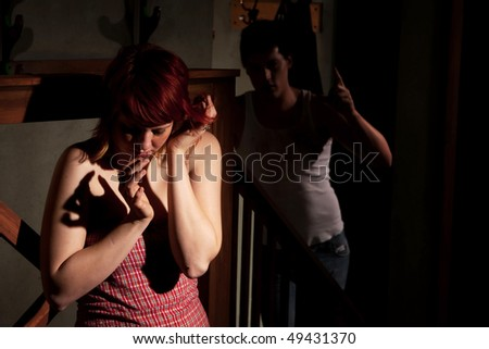 Woman in room with abusive man - stock photo