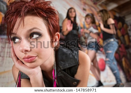 Woman in 20's looking up with group laughing in background - stock photo