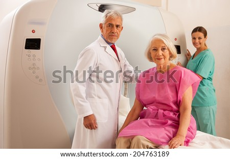 Woman in 60s ready to be checked under mri scanner with senior doctor and smiling female assistant. - stock photo
