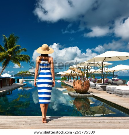 Woman in sailor striped dress near poolside jetty at Seychelles - stock photo