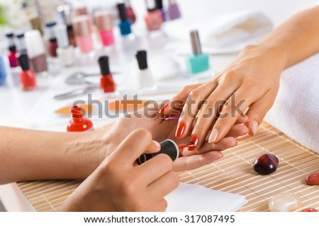 Woman in salon receiving manicure by nail beautician - stock photo