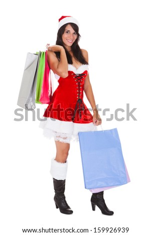 Woman In Santa Claus Costume Holding Shopping Bags Over White Background
