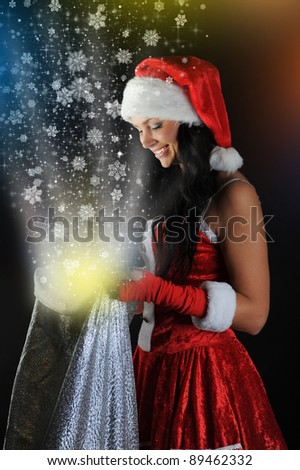 Woman  in Santa Claus hat smiles and holding a gift in magic bag on a dark background - stock photo