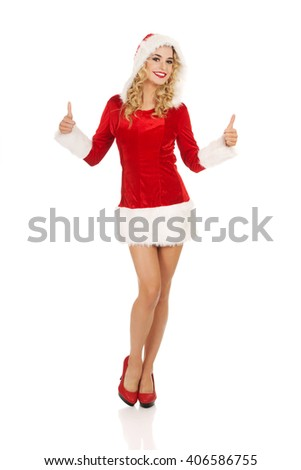 Woman in santa clothes gesturing thumbs up - stock photo