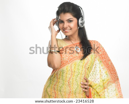 Woman in sari listening to music with head phones - stock photo