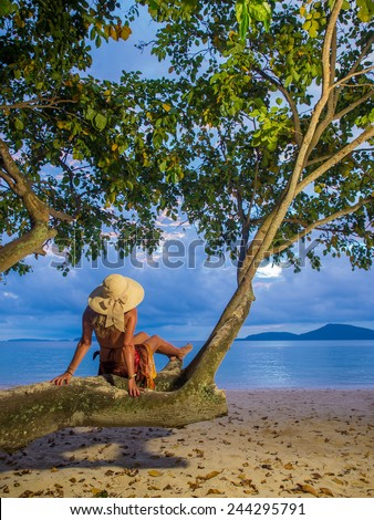Woman in sarong on a tree at the  beach  in Thailand - stock photo