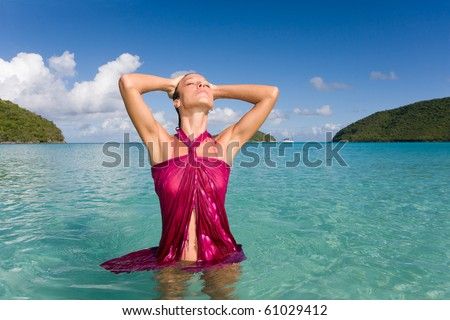 woman in sarong serene and happy in tropical waters - stock photo