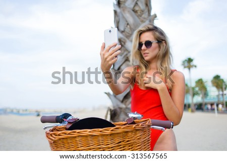 Woman in sexy bikini making self portrait with a cell phone camera while sitting on classic bicycle at summer vacation,charming female in fashion sunglasses taking a picture of herself on smart phone - stock photo