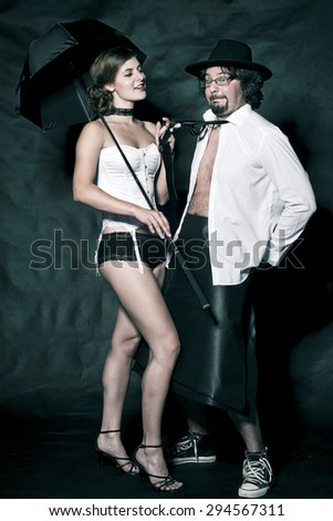 Woman in sexy costume and man in white shirt with black tie and hat