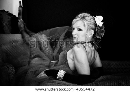 woman in sexy outfit looking back over her shoulder at viewer, with her feet up. - stock photo