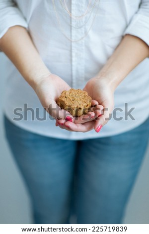 Woman in shirt and jeans holding cake - stock photo