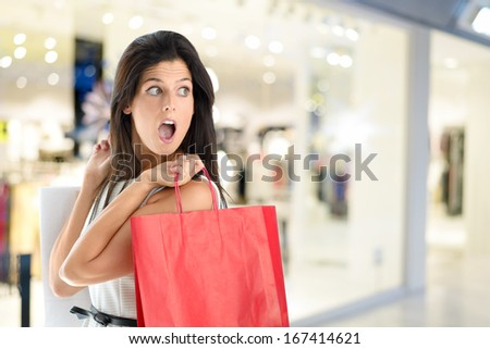 Woman in shopping center with bags. Fashion girl in mall looking surprised on shopwindow background. - stock photo