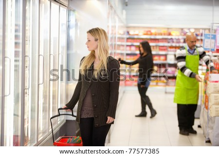 Woman in shopping mall looking through cooler window with people in the background - stock photo