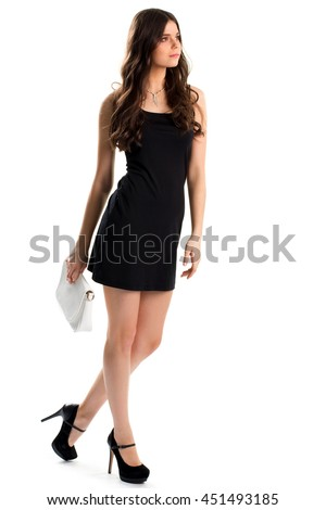 Woman in short black dress. Dark shoes on high heels. Designer apparel and expensive jewelry. Young and pretty model.