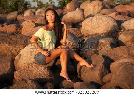 Woman in shorts sitting on stones - stock photo