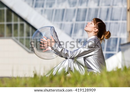 Woman in silver astronaut costume standing on the grass and inhaling fresh air - stock photo