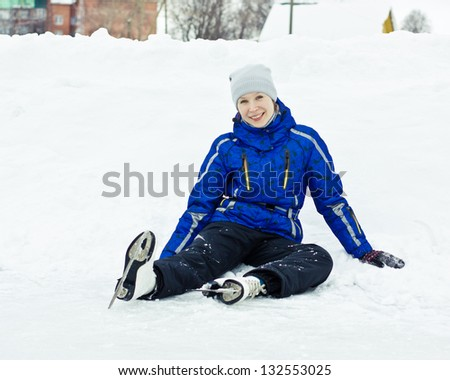 Woman in skates sitting on the ice smiling. - stock photo