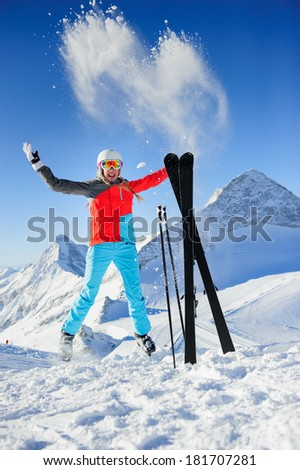 Woman in Ski resort jumping and smiling - stock photo