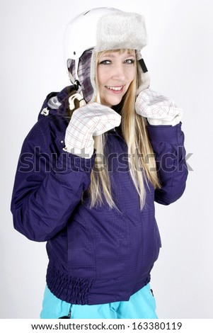 Woman in skiing suit wearing a protective helmet - stock photo