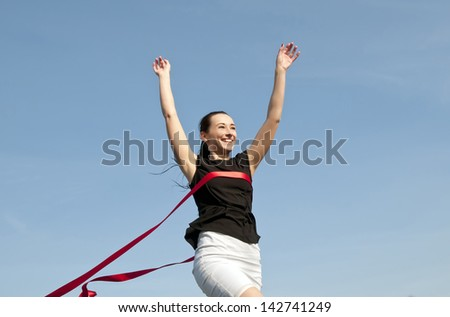woman in skirt crossing finishing line - stock photo