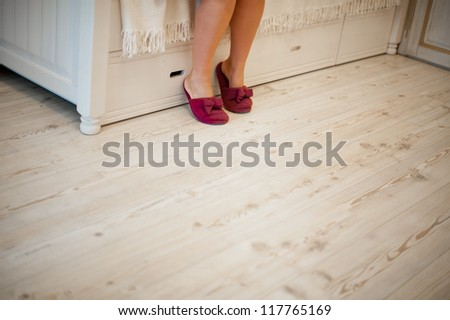 woman in slippers sitting on the bed